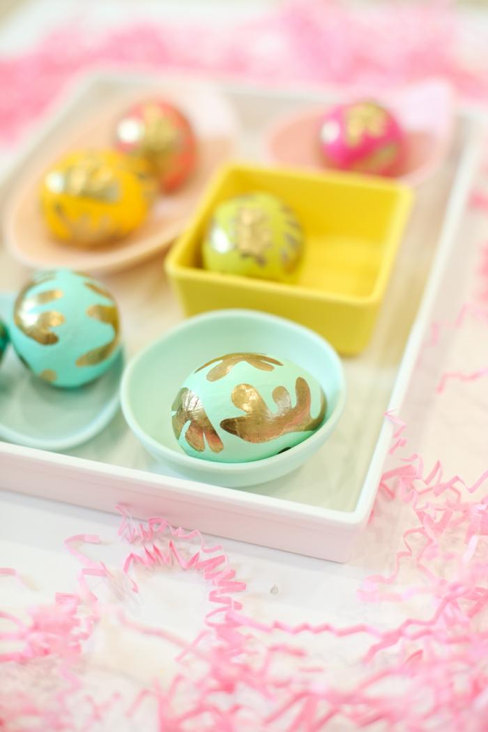 Ostereier dekorieren, zwei rosa, zwei gelbe und zwei blaue Eier mit goldener Farbe dekoriert