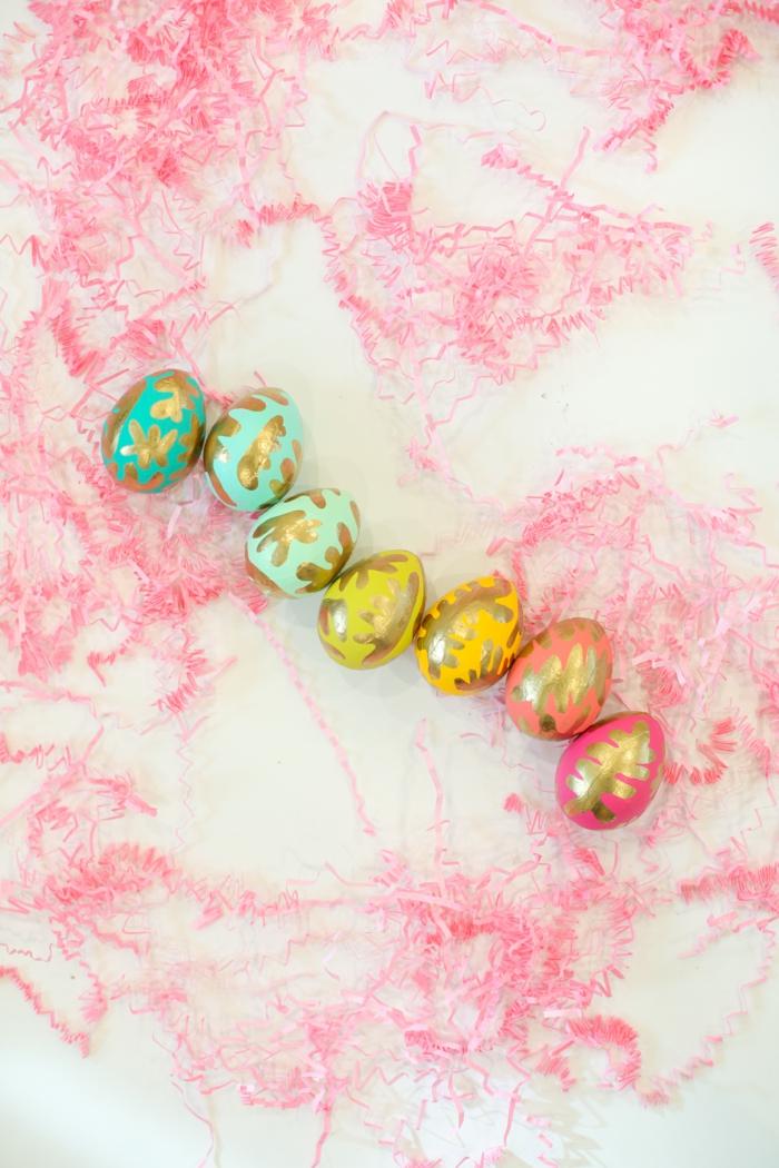 eine Reihen von bunten Eier, Ostereier dekorieren mit goldener Farbe wie Blätter