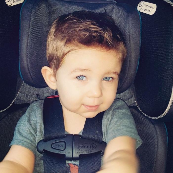 ein kleiner Herr im Kindersitz im Auto, schnelle und einfache Frisur Junge
