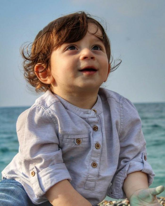 niedliche Frisuren für Jungs, ein Baby mit grauem Hemd, gekrauste braune Haare