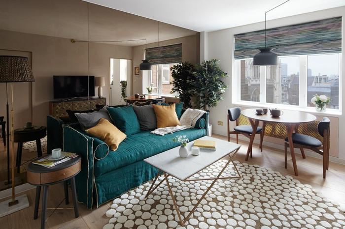 kleine Räume einrichten, blaues Sofa, Teppich auf weißen Flecken, in einer Einzimmerwohnung