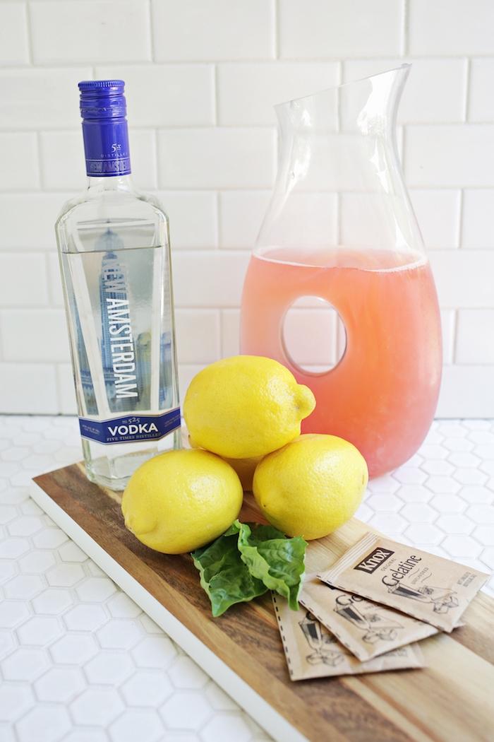 ein holzbrett, ein großer krug aus glas und mit einer pinken limonade, eine flasche mit vodka und drei große gelbe zitronen und minze mit grünen blättern, eine weiße wand mit weißen fließen, eine orangen limonade selber machen