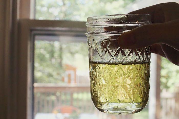 einen cocktail mit einer hausgemachten limonade, eine hand mit einer glas mit einer gelben limonade und ein fenster, eine amerikanische limonade rezept