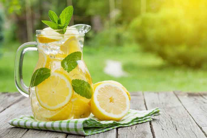 ein tisch aus holz und mit einer kleinen grünen serviette, ein großer krug aus glas mit einer gelben limonade mit eis und mit vielen kleinen gelben zitronen, minze mit grünen blättern