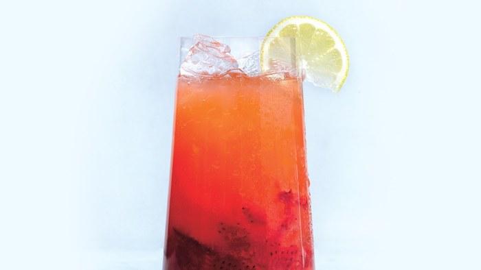 ein glas mit einer roten hausgemachten limonade mit eis und einer kleinen gelben zitrone, eine orangen limonade selber machen