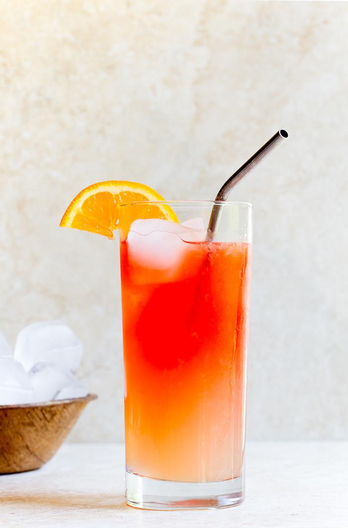 ein glas mit einem schwarzen strohhalm, eis und orangen, eine orangen limonade selber machen