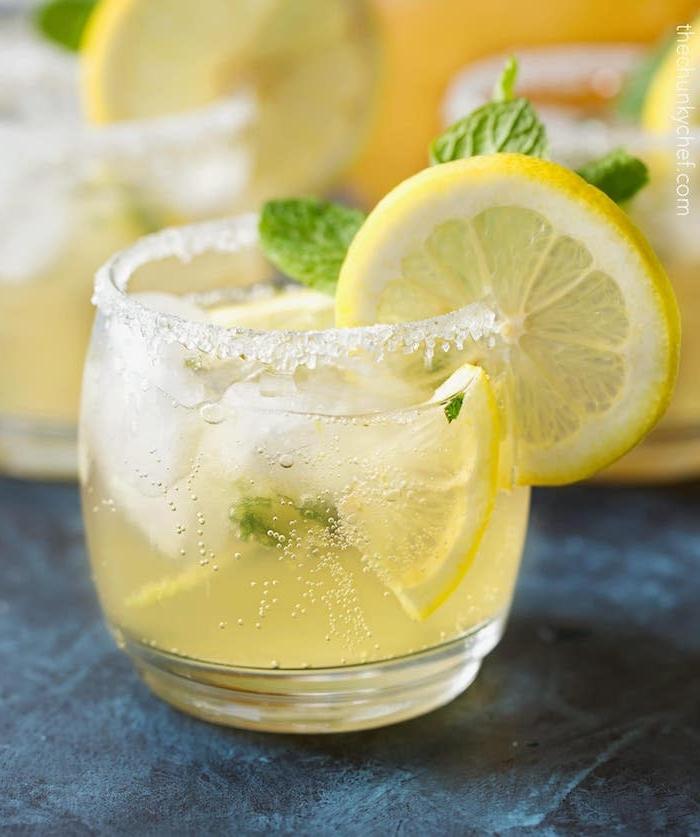 limonade rezept, ein glas mit zucker und einer selbstgemachten amerikanischen gelben limonade mit eis, gelben zitronen und minze mit grünen blättern