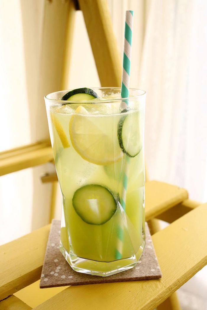 ein glas mit einer erfrischungsgetränk mit vielen kleinen grünen gurken und gelben zitronen und mit einem blauen strohhalm, eine hausgemachte limonade