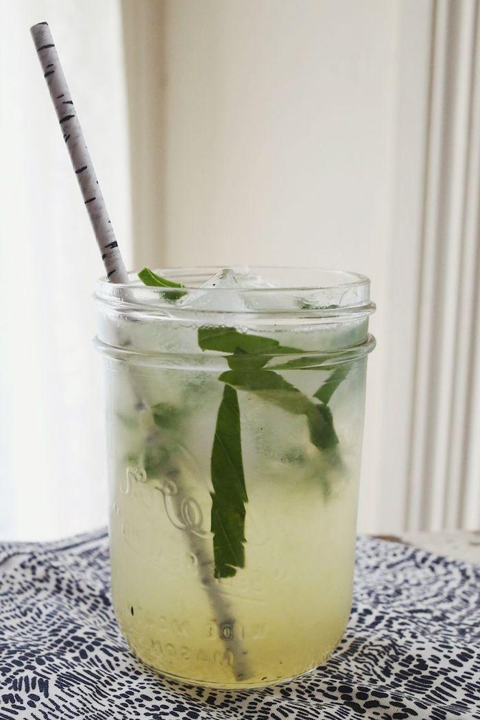 eine weiße birke, ein glas mit einem weißen strohhalm und einer hausgemachten limonade mit eis und mit minze mit grünen blättern, eine zitronenlimo selber machen