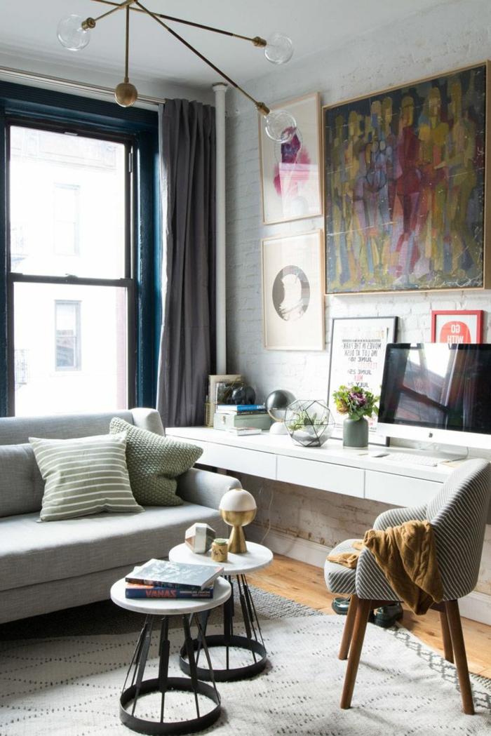 einige gerundete Lampen, runde Tische, ein Bild, ein graues Sofa, kleines Zimmer einrichten