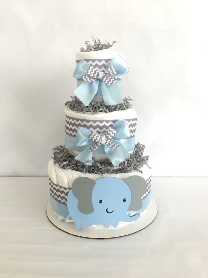 eine weiße dreistöckige windeltorte basteln, ein blauer elefant mit zwei grauen ohren und schwarzen augen und große graue und blaue schleife und weiße windel