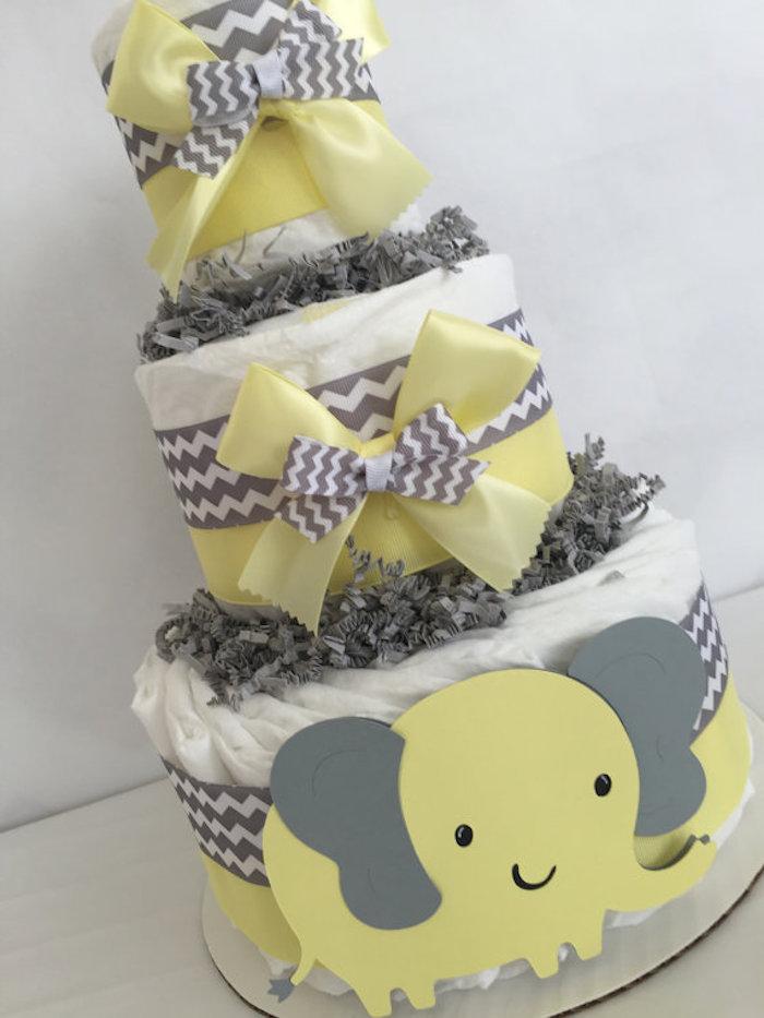 eine torte aus vielen weißen windeln, eine windeltorte basteln, ein großer gelber elefant mit grauen ohren und schwarzen augen, eine windeltorte mit gelben und grauen schleifen
