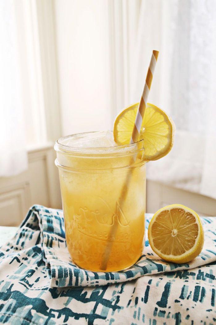 ein fenster und ein tisch mit einer blauen decke, ein glas mit einer selbstgemachten limonade mit eis und mit gelben zitronen und einem langen strohhalm, eine zitronenlimonade selber machen