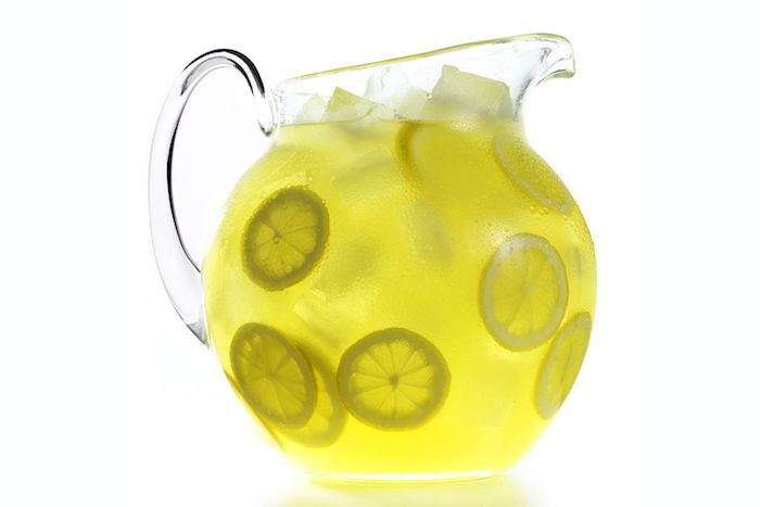 großer krug aus glas, eine hausgemachte limonade mit vielen kleinen gelben zitronen und mit eis