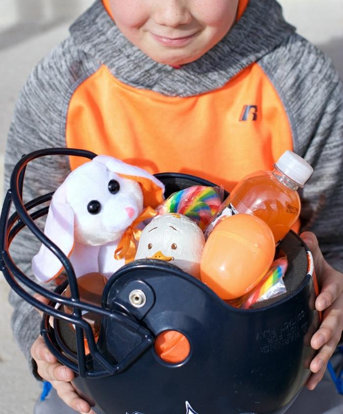 ein Helm als Osterkörbchen, voller Süßigkeiten, Getrenke und Kuscheltier