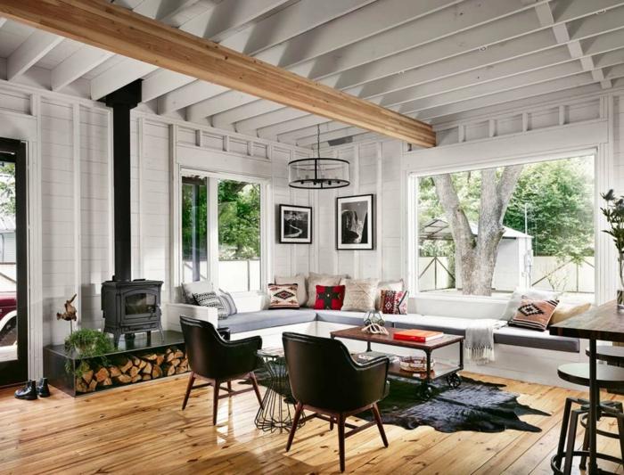 ein Ecksofa in hellblauer Farbe, zwei braune Stühle, Einzimmerwohnung, kleines Zimmer einrichten