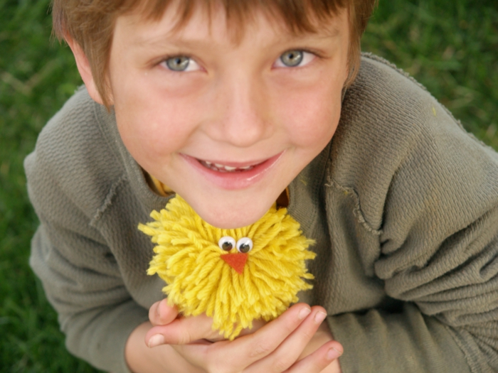 ein Junge hat ein Küken aus Garn in Hände, Ostergeschenke selber machen