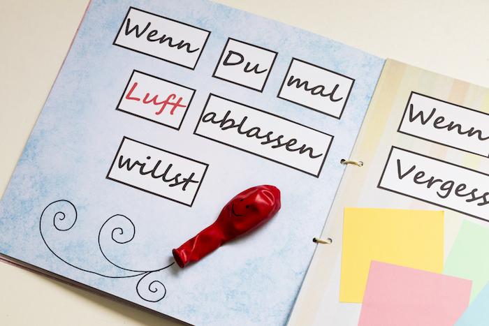 kleines diy wenn buch aus papier und mit kleinen blauen, grünen, gelben und pinken zetteln und einem kleinen roten ballon mit schwarzen augen
