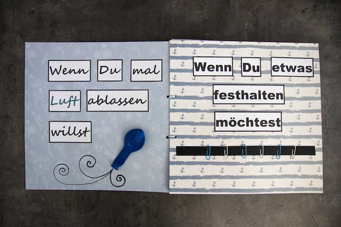 ein kleines selbstgebasteltes wenn buch aus papier und mit einem kleinen blauen ballon mit schwarzen augen, wenn buch ideen, ein wenn buch mit kleinen grünen, gelben zbd blauen klammern und kleinen ankern