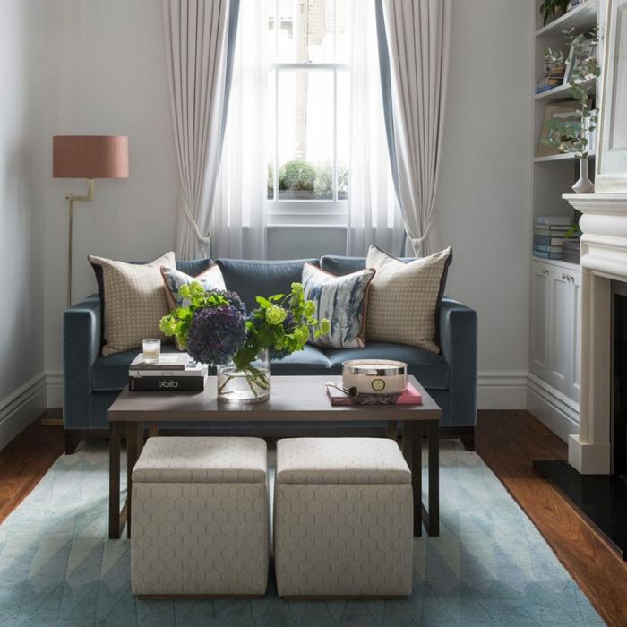 eine blaue Couch, symmetrisch gelegte Kissen, zwei Hocker, kleines Wohnzimmer einrichten