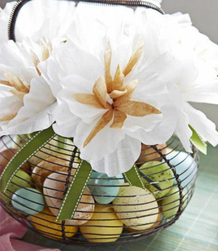ein Osterkörbchen aus Draht voller Ostereier, Edelweiße aus Papier als Deko