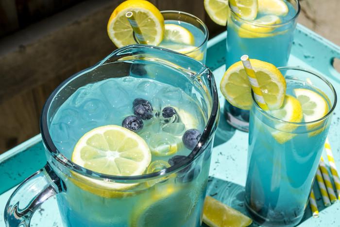 drei kleine blaue gläser mit einer blauen limonade mit eis, vielen gelben zitronen und mit drei gelben strohhalmen, eine hausgemachte limonade