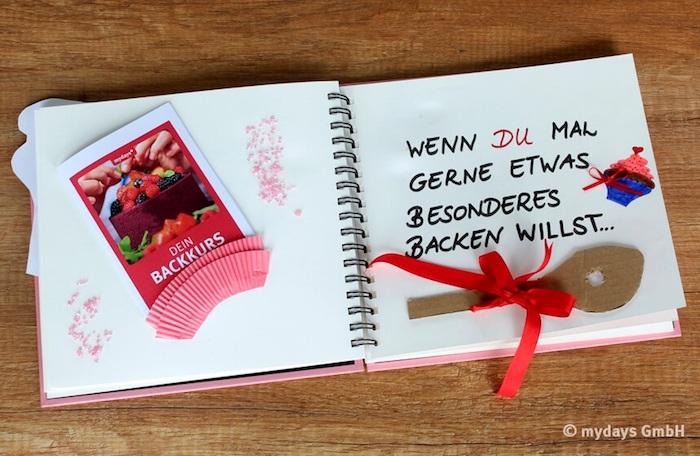 ein tisch aus holz und ein kleines pinkes wenn buch mit einem braunen papierlöffel, zwei roten schleifen, einem kleinen kuchen mit einem kleinen roten herzen