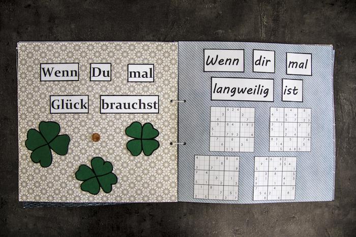 kleines wenn buch mit grauen und beigen seiten, klee mit vier grünen blättern, wenn buch sprüche, vier sudoku spiele