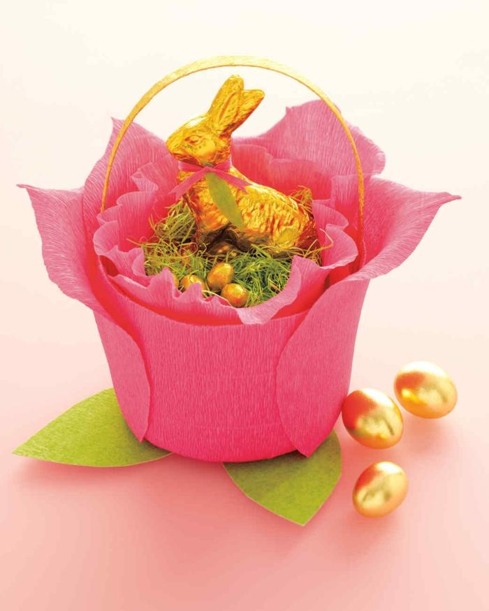 ein Körbchen wie rosa Rose dekoriert, voller Süßigkeiten mit goldenen Verpackungen, Ostergeschenke selber machen