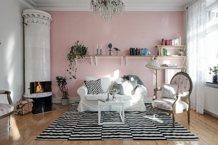 ein weißes Sofa, gestreifter Teppich, ein Kamin in der Ecke, kleine Wohnung einrichten