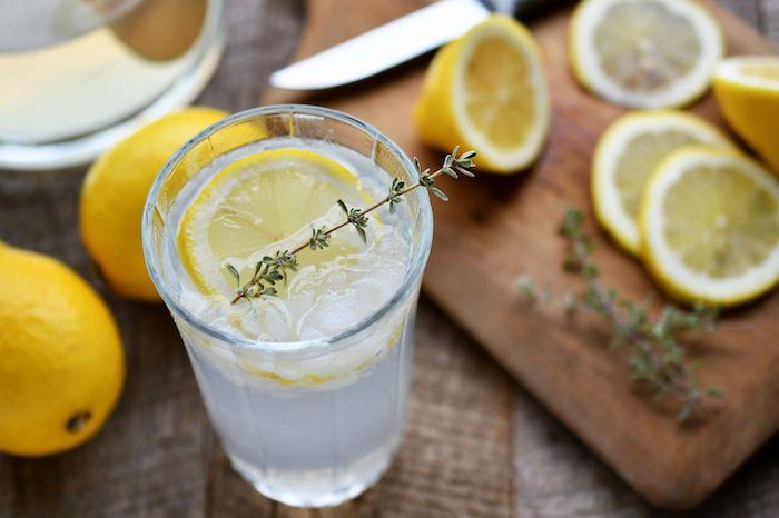 ein messer und ein holzbrett, ein glas mit gelben zitronen, eine amerikanische hausgemachte limonade