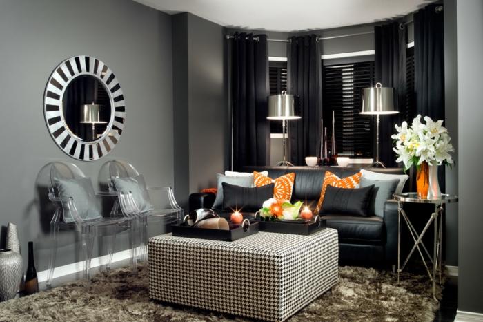schwarzes Sofa, orange und blaue Kissen, karrierter Tisch, ein runder Spiegel, kleine Wohnung einrichten