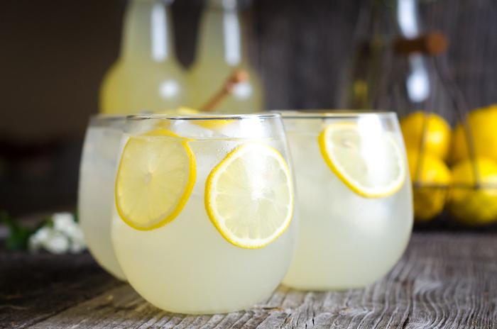 drei kleine gläser mit eis und kleinen gelben zitronen, eine hausgemachte limonade, eine erfrischungsgetränk selber machen