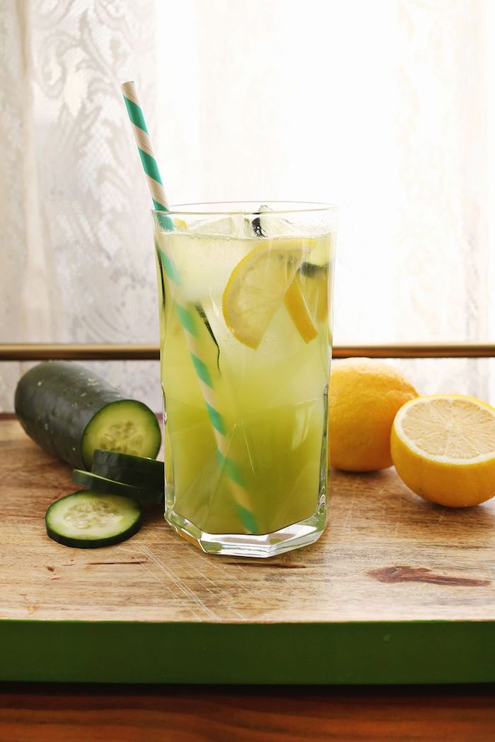 ein fenster und ein schneidebrett, ein glas mit einer grünen limonade mit grünen gurken, eis und mit vielen gelben zitronen, eine limonade selber machen