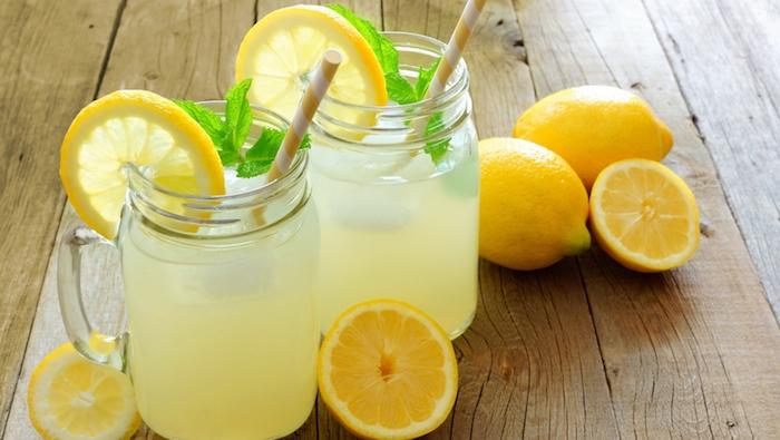 viele kleine gelbe zitronen, ein tisch aus holz und zwei gläser mit einer gelben limonade mit vielen kleinen zitronen und minze mit vielen grünen blättern