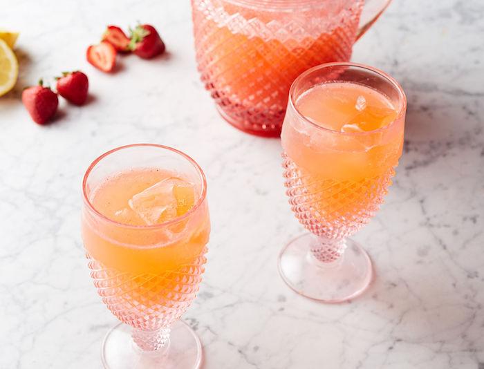 ein krug mit einer hausgemachten limonade mit eis, ein tisch und rote erdbeeren und gelbe zitronen, orangen limonade selber machen