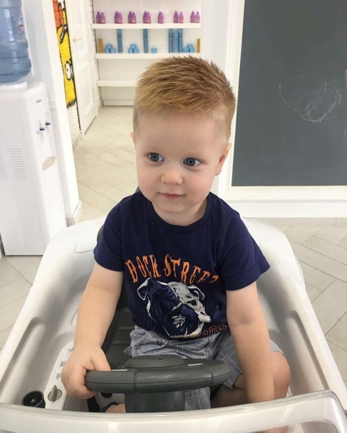rothaariges Kleinkind in einem Spielauto, seitlich rasiert, längeres Haar am Oberkopf