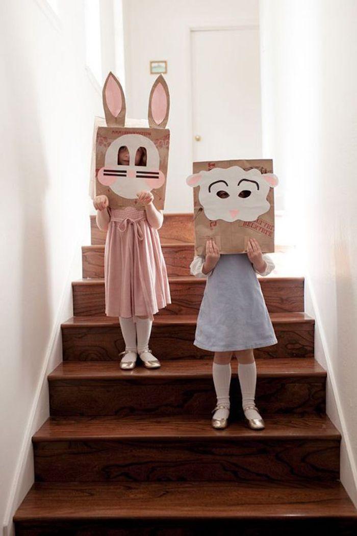 zwei mädchen mit blauen und pinken kleidern, eine braune treppe aus holz und weiße wände, hasen masken mit pinken hasenohren aus papier, lustige osterbilder für kinder