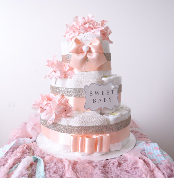 eine dreistöckige torte aus windeln und mit vielen pinken blumen und großen schleifen, windeltorte mädchen selber machen