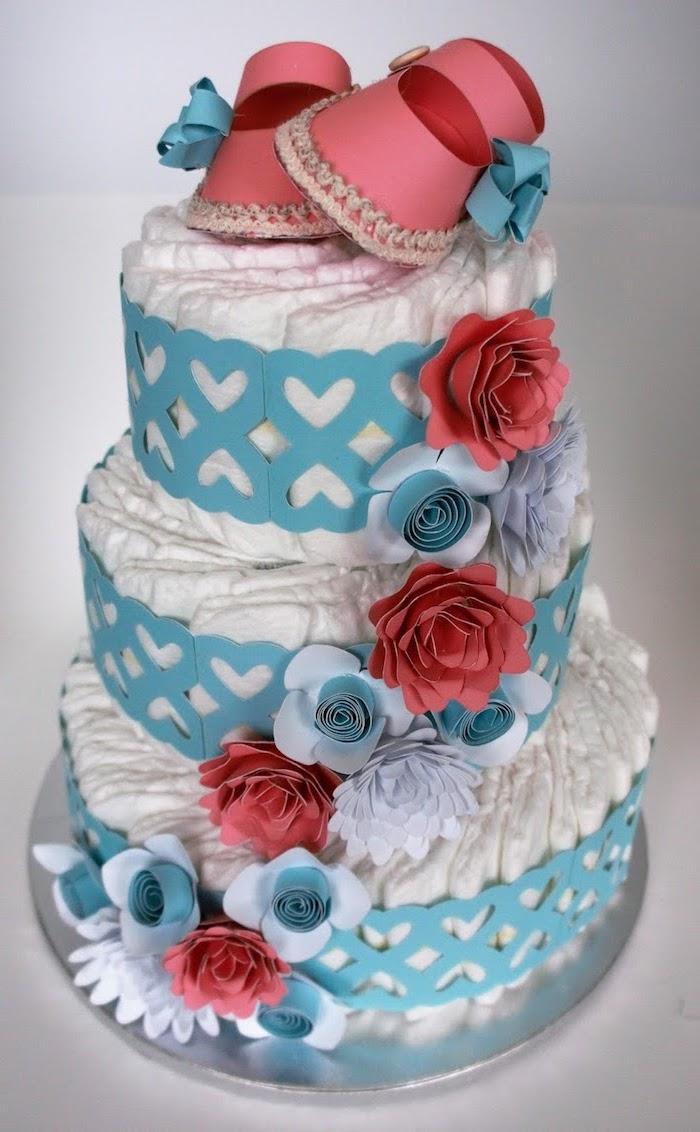 pinke baby schuhe, eine dreistöckige große torte aus vielen weißen windeln und mit großen roten, blauen und violetten blumen und weißen herzen, eine windeltorte selber machen