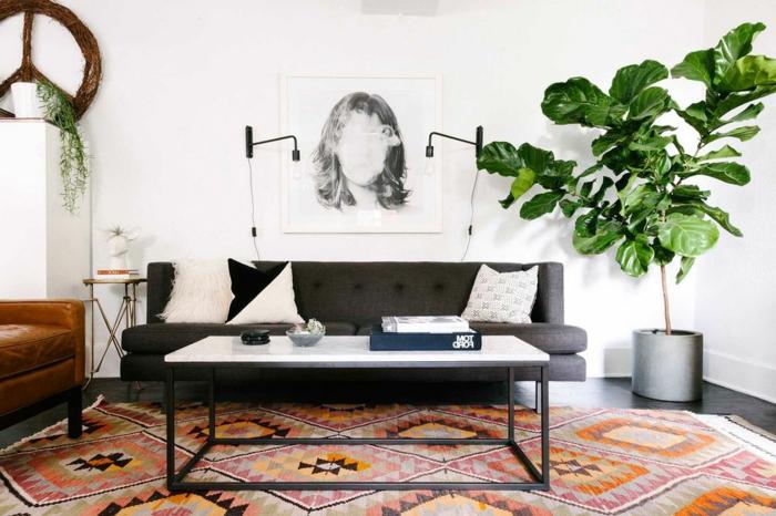 eine grüne Pflanze in der Ecke, schwarzes Sofa, weiße Kissen, bunter Teppich, Zimmer einrichten Ideen