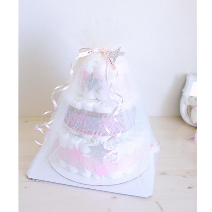 anleitung windeltorte, eine große weiße dreistöckige torte aus vielen weißen windeln und mit einer violetten schleife und grauen und pinken sternen