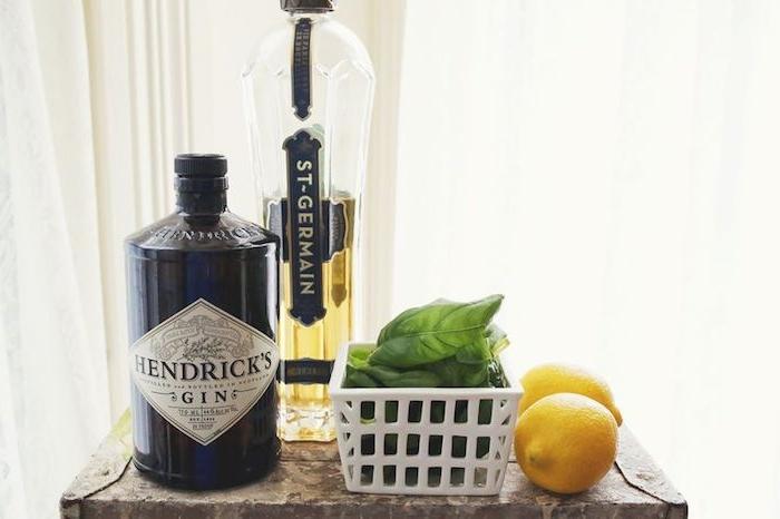 eine große schwarze flasche mit gin, ein kleiner tisch aus holz, zwei große gelbe zitronen und minze mit grünen blättern