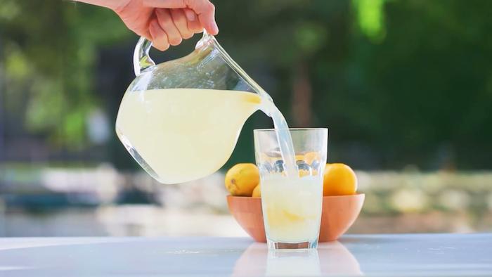 ein garten und ein tisch, eine hand mit einem grpßen krug mit einer gelben limonade, eine orange schüssel mit gelben zitronen, eine hausgemachte limonade