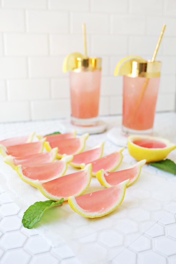 zwei gläser mit zwei gelben strohhalmen und mit gelben zitronen, eine pinke hausgemachte limonade mit vielen gelben zitronen