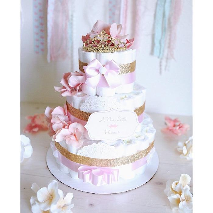 ei tisch aus holz und eine dreistöckige torte aus vielen windeln und mit kleinen pinken schleifen und rosen und krone, eine windeltorte mädchen selber machen