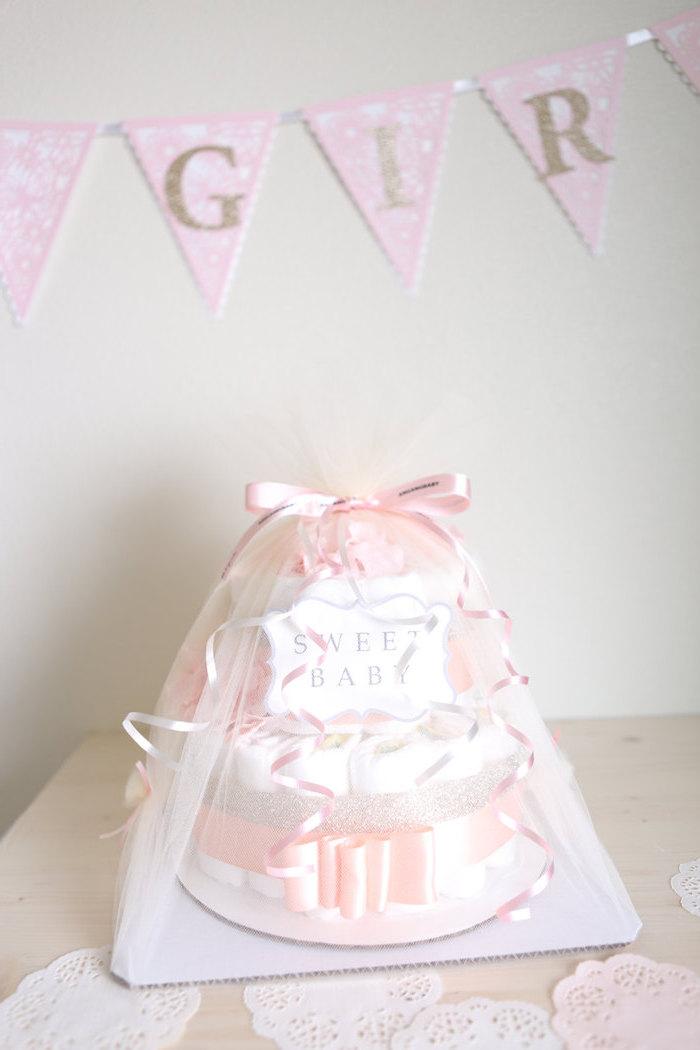 ein tisch aus holz und eine zweistöckige torte aus vielen windeln und mit pinken schleifen, eine windeltorte bastelanleitung