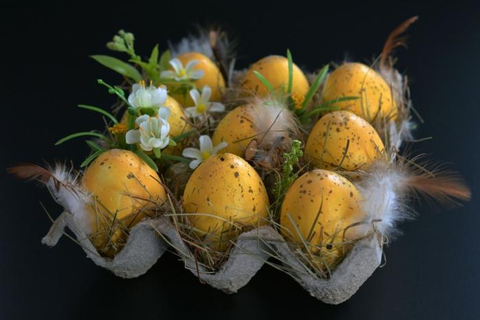 gelbe Ostereier natürlich färben, ein Karton voller Feder, kleine Blumen und Gras