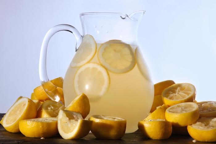 ein großer krug mit einer gelben hausgemachten amerikanischen limonade und mit vielen gelben zitronen, eine amerikanische zitronenlimonade selber machen