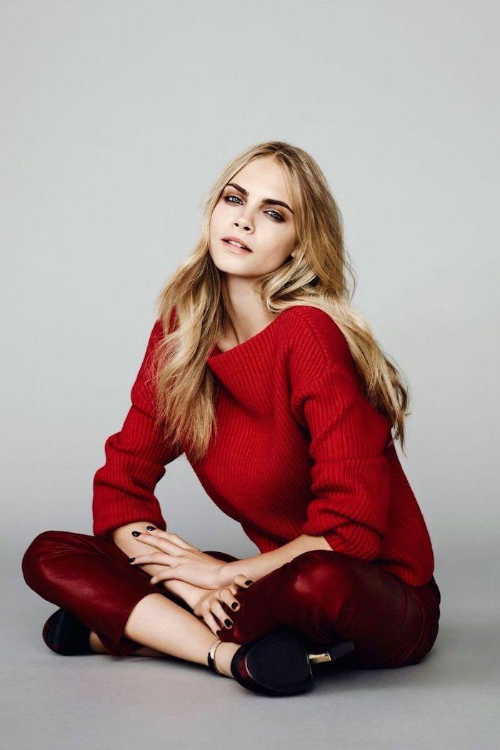Cara Delevigne Langhaarfrisur, blonde Haare, knallroter Pullover, weinrote Hose und High Heels, schwarzer Nagellack